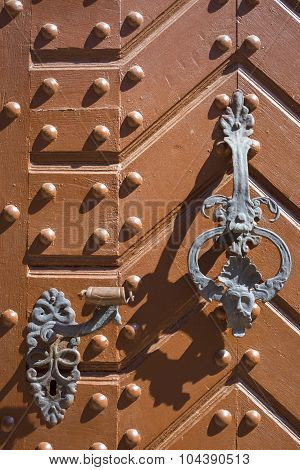 Wrought-iron bell and handle on orange door with metal rivets