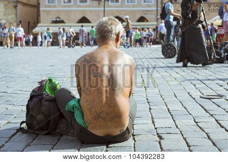 Naked beggar with a tattoo on her back