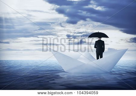 Asian Business Man Holding Umbrella Standing On The Paper Boat