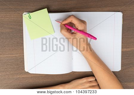 Open copybook with writing hand on table