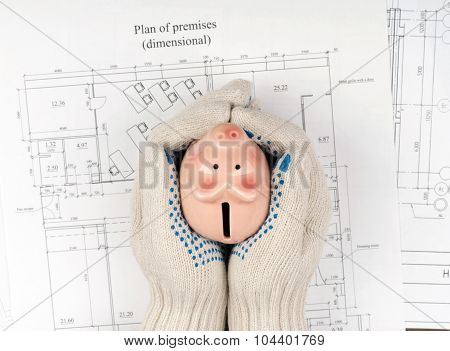 Mans hands in gloves holding piggy bank, top view