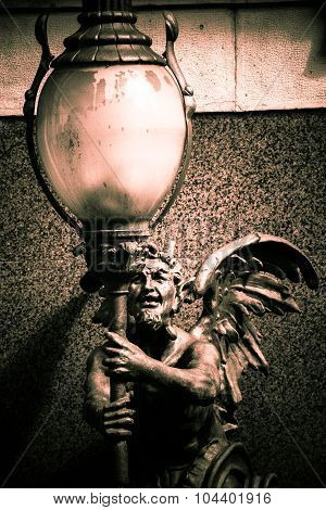 Statue of a demon holding a lamppost