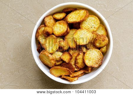 Fried colocasia vegetable kept in a stainless steel container on a plain background