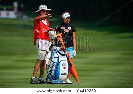 KUALA LUMPUR, MALAYSIA - OCTOBER 09, 2015: South Korea's Mi Hyang Lee discusses with her caddy on the fairway of the KL Golf & Country Club at the 2015 Sime Darby LPGA Malaysia golf tournament.
