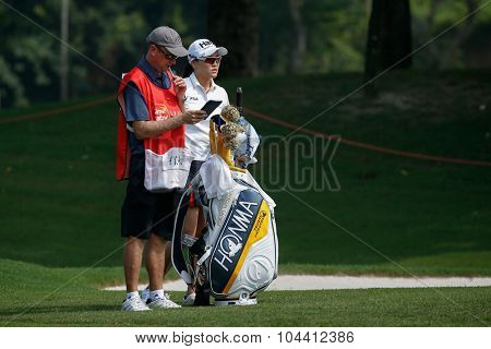 KUALA LUMPUR, MALAYSIA - OCTOBER 09, 2015: South Korea's Ryu So Yeon discusses with her caddy on the fairway of the KL Golf & Country Club at the 2015 Sime Darby LPGA Malaysia golf tournament.