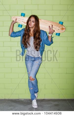 Beautiful Long-haired Girl With A Wooden Longbord Near A Green Brick Wall