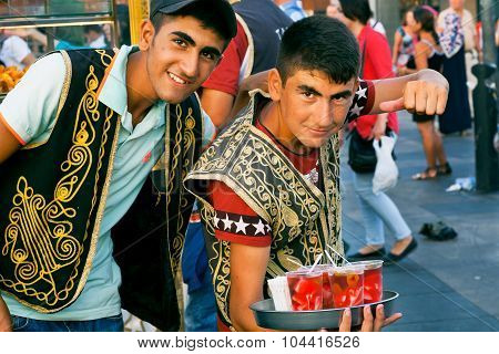 Young vendors in the Turkish clothes selling drinks