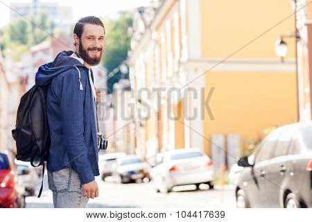 Handsome bearded tourist is sightseeing in city