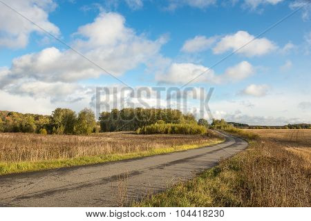 Country Road And Cumulus Clouds Over The Retracted Fields