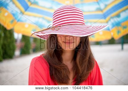 Girl In The Hat Under Umbrella On The Sand