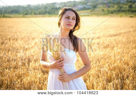 Girl In A Field Holding Spikes At Sunset