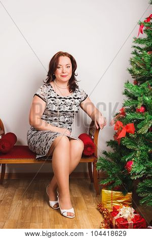 Lovely woman sits on ottoman
