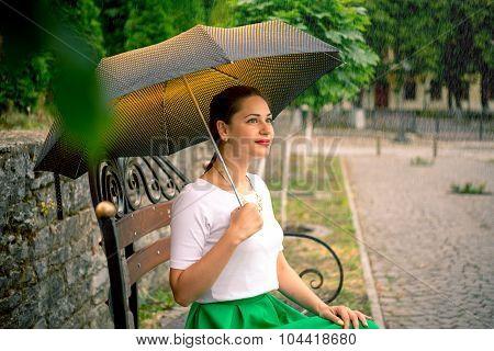 Girl Under Umbrella Sitting On Bench