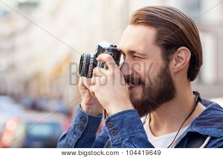 Attractive bearded man is making photos of city