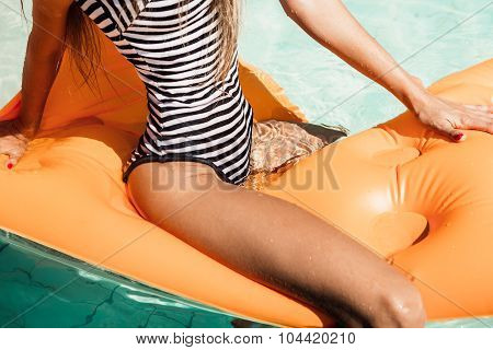 Sexy Young Woman In A Swimsuit Sits Astride On An Inflatable Mattress In The Pool