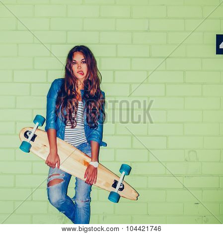 Beautiful Long-haired Lady With A Wooden Long Skateboard Near A Green Brick Wall