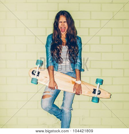 Beautiful Long-haired Woman With A Wooden Long Skateboard Near A Green Brick Wall
