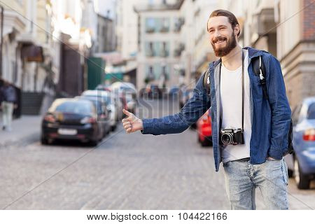 Handsome young male hitchhiker is trying to stop car