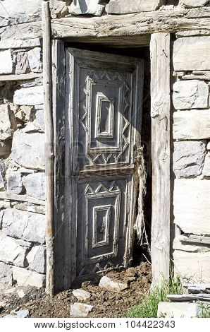 Open Wood Door With Ornaments On Cowshed In Old  Stone House
