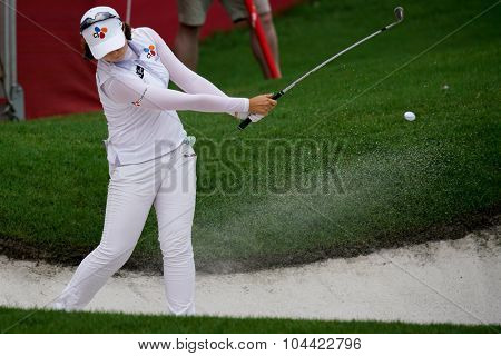 KUALA LUMPUR, MALAYSIA - OCTOBER 09, 2015: South Korea's Q Baek plays out of the sand bunker in the 18th hole green at the KL Golf & Country Club at the 2015 Sime Darby LPGA Malaysia golf tournament.