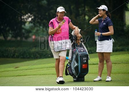 KUALA LUMPUR, MALAYSIA - OCTOBER 10, 2015: China's Xi Yu Lin takes a break with her caddy in-between plays at the KL Golf & Country Club during the 2015 Sime Darby LPGA Malaysia golf tournament.