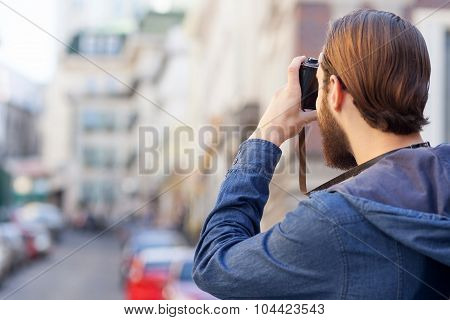 Cheerful bearded photographer is making photos of town