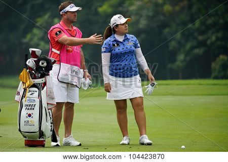KUALA LUMPUR, MALAYSIA - OCTOBER 10, 2015: South Korea's Inbee Park discusses with her caddy on the fairway at the KL Golf & Country Club at the 2015 Sime Darby LPGA Malaysia golf tournament.