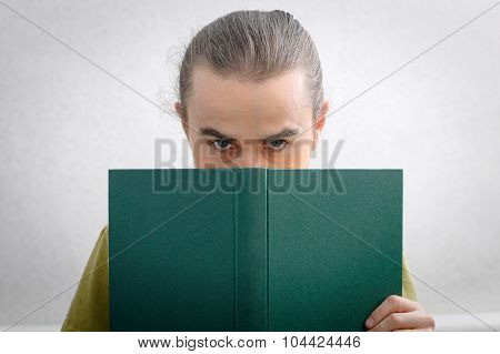 Young Man Peeping From Behind The Book