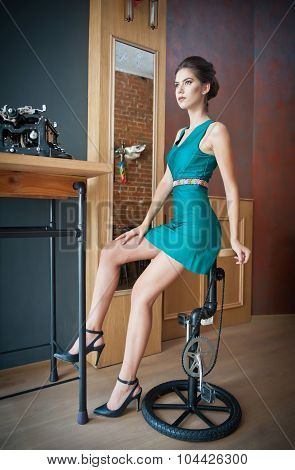Fashionable attractive young woman in short tight fit green dress sitting in restaurant on chair