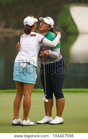 KUALA LUMPUR, MALAYSIA - OCTOBER 10, 2015: Amy Yang (black pants) hugs Chella Choi at the end of Round 3 of the 2015 Sime Darby LPGA Malaysia golf tournament played at the KL Golf & Country Club.