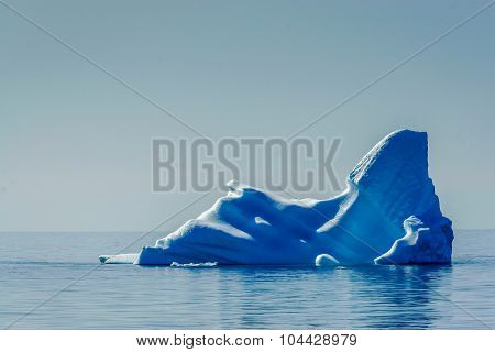 Lone, powerful deep blue iceberg