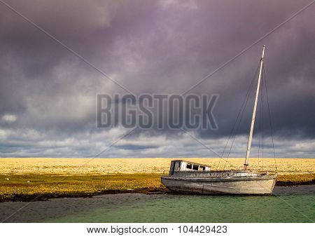 Abandoned, wooden fishing boat on the beach in the Arctic