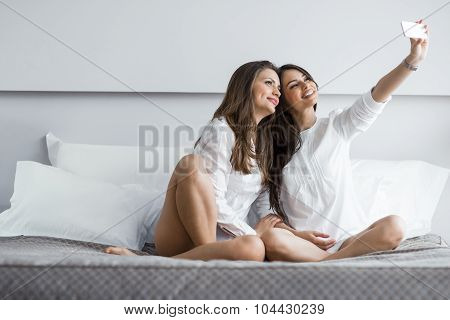 Two Hot Girls Lying  On A Bed Taking A Photo Of Themselves With A Phone