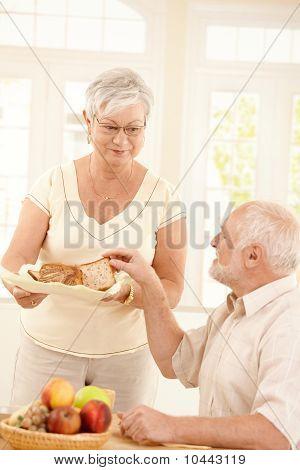 Older Wife Serving Bread For Breakfast
