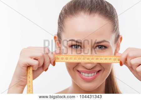 Attractive young fit girl with tape measure