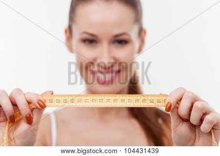 Cheerful young woman is talking measurements of her figure