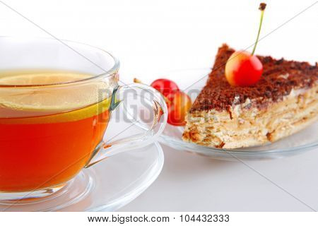 golden tea, chocolate cake and cherry on white
