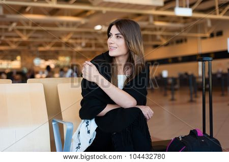 Airport Young female passenger at gate waiting in terminal while waiting for her flight.