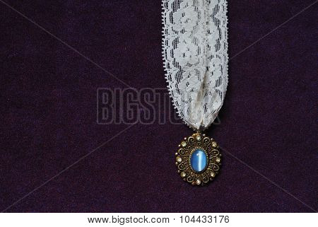 moonstone necklace with white lace on purple velvet background