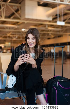 Young female passenger on smart phone at gate waiting in terminal
