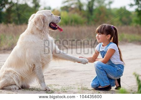 Cheerful small female child with pet in park