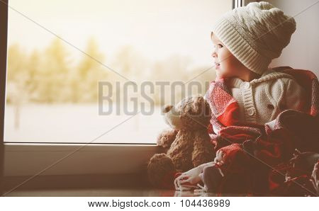 Child Little Girl With  Teddy Bear At Window And Looking At Winter Forest