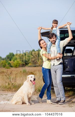 Pretty parents and child with puppy near vehicle