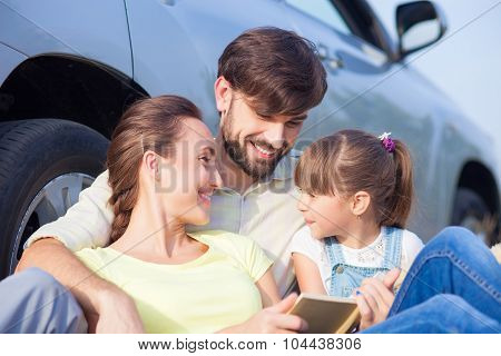 Cute family is resting in nature near transport