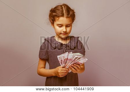 teen girl of European appearance holds five denominations of mon