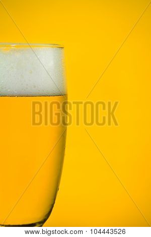 Beer In A Glass On Yellow Backlight Background, Soft Focused, Close-up