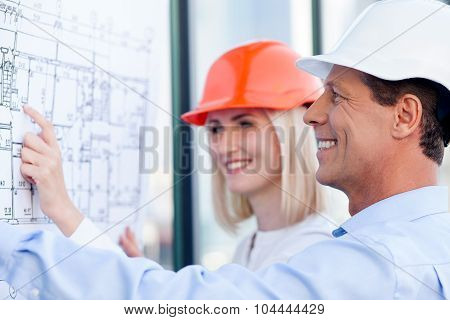 Cheerful engineers are discussing plan of building