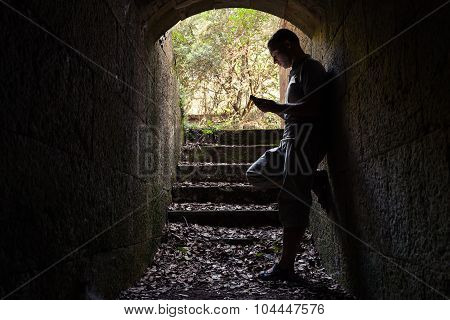 Young Man Works On A Smartphone In Dark Tunnel