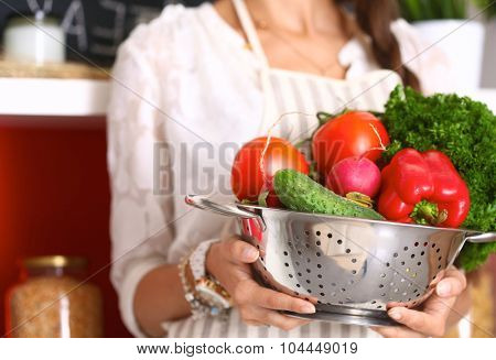 Young woman holding vegetables standing in kitchen