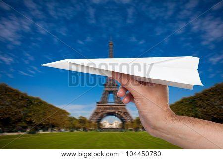 Hand trowing a paper plane in Paris